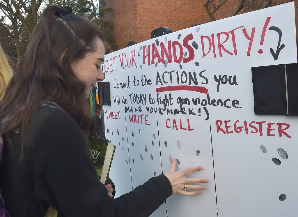 . PETE  BANNAN-DIGITAL FIRST MEDIA        Haverford High School junior Emily Selfridge puts her thumbprint on the commitment to call elected officials in support of gun control at a morning rally at the high school.