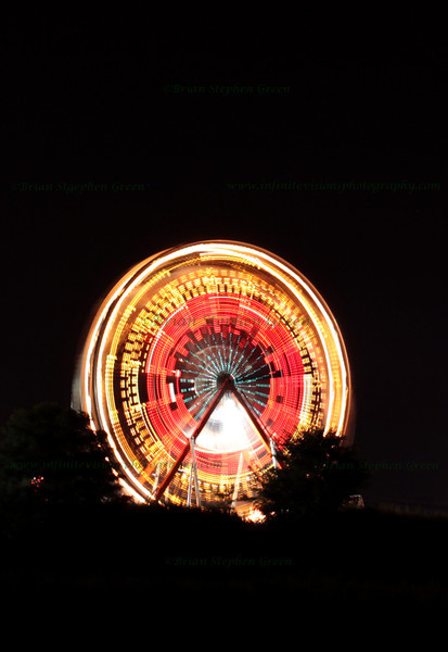 """Ferris Wheel"" 7/29/11<br /> At a local carnival last weekend.  Gotta love ferris wheels, especially for long exposures.  Was actually in a field a bit outside the carnival for this shot waiting for the fireworks to begin; turns out I managed to position myself about 100 yards from the launch site... moved real quick after the first rocket went off :)  Slightly uneven ground and I think my tripod shifted a tad during the exposure, but I liked the patterns and colors.<br /> Another Friday... Hope it is a great one!"