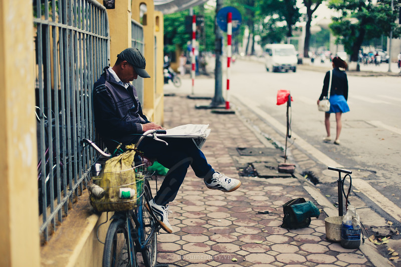Ông sửa xe đạp ngồi bờ rào đọc báo