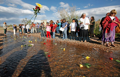 People throw flowers in the Santa Fe river during the blessing of the San Isidro river crossing on May 18, 2010. San Isidro, the patron saint of farmers, is asked for his blessing for good weather and prosperous crops.  Farmers in the Village of Agua Fria once depended upon the the Santa Fe River to grow crops for their families and to sell their goods in the city.               Luis Sanchez Saturno/ The New Mexican.