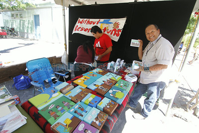 """People walk past Ed Singer's booth, a navajo artist from Northern AZ, at the Rail Yard Park durin the first annual  Indigenous Fine Arts Market on Thursday, August 21, 2014. The painting outside Singer's booth is called """"Bone Weapon."""" Luis Sanchez Saturno/The New Mexican"""