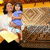 "Lola Cody, Navajo, who won best of show with her textiles ""Sands of No Water Mesa"" rug during a ceremony at the Santa Fe Convention Center on Friday, August 22, 2014 holds her granddaughter, Reese Cody, 21 months. Jane Phillips/The New Mexican"