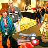 From left, Robyn Hetrick and Gary Ruttenberg from Los Angeles view the winning categories during the Best of Show ceremony at the Santa Fe Convention Center on Friday, August 22, 2014. They have been coming to market for 30 years.  Jane Phillips/The New Mexican