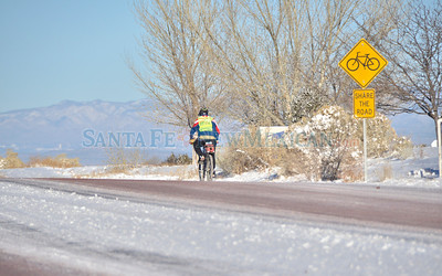 A brave cyclist makes his way along snow and ice covered Avenida Vista Grande on a very cold Monday morning in Eldorado, December 10, 2012.  Clyde Mueller/The New Mexican