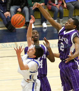 Matthew Barela (left), of St. Michael's goes up for a rebound against (background) DJ Blackmon and (right) John Dawson of Clovis during a boys basketball game in Santa Fe, N.M. on Dec. 10, 2011.  Natalie Guillén/The New Mexican