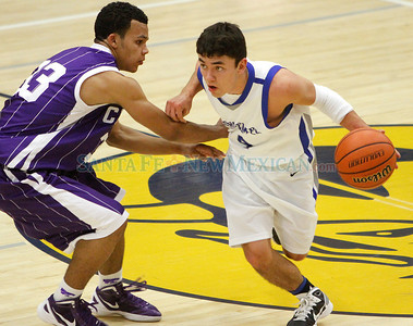 Antonio Garcia (right) gets around Aaron Steward (left) of Clovis High School during a boys basketball game in Santa Fe, N.M. on Dec. 10, 2011.  Natalie Guillén/The New Mexican