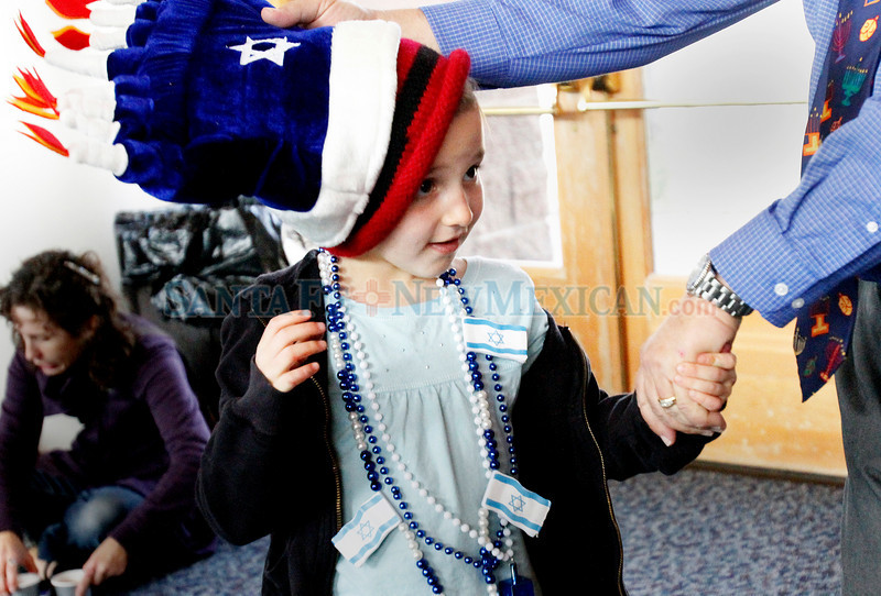Rabbi Marvin Schwab helps Deedee Jansen, 7, with her hat at Temple Beth Shalom where there was a latke lunch in Santa Fe on Dec. 5, 2010. <br /> Natalie Guillen/The New Mexican