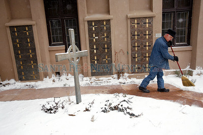 Sexton, Bill Adrian, sweeps the snow in the garden at Church of Holy Faith on Wednesday, February 2, 2011.  Bitterly cold weather is expected for the next few days. Photos by Jane Phillips/The New Mexican