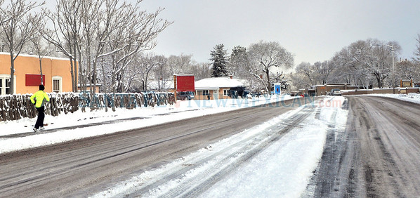 A jogger runs on a snow covered side walk on Paseo de Peralta as motorists negotiated slippery ice covered roads in Santa Fe, New Mexico after receiving a snow fall of 2 to 3 inches on Friday February 3, 2012.  Clyde Mueller/The New Mexican