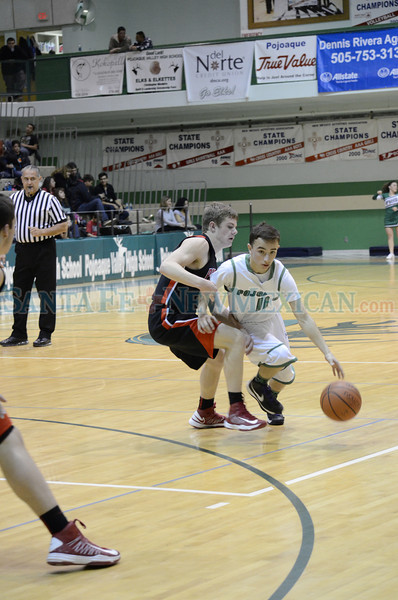 Grants' Keegan Stewart, number 11, covers Pojoaque's Anthony Rodriguez, number 11, during the first quarter of the Grants vs Pojoaque boys basketball game at Pojoaque High School on Jan. 16, 2013. Photo by Erika Serrano/For The New Mexican