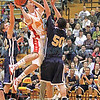Santa Fe's Orlando Echave, number 50, tries to block Española's Antonio Romero, number 24, during the first quarter of the Española Valley High School vs Santa Fe High School at Española on Jan. 19, 2011.          Photos by Luis Sanchez Saturno/The New Mexican