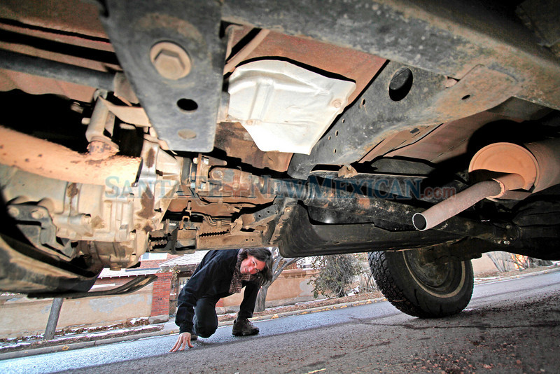 Alexander Wolf, from Santa Fe, looks under his 1987 Toyota 4Runner outside his home on Jan. 7, 2011. Wolf, like many others across the country, had his catalytic converter stolen for the precious metals in it. The theft occured outside his house on Tuesday morning.          Photos by Luis Sanchez Saturno/The New Mexican