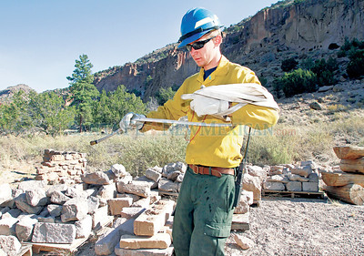 Firefighter, Jake Wilson, from Washington State, breaks down temporary protection at  Bandelier National Park on Wednesday, July 6,2011.  Wilson just received his red card and has been working the past six days. Photos by Jane Phillips/The New Mexican