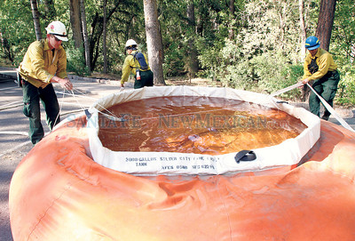 Bandelier National Monument  Firefighters from left, Stewart Robertson, Lucy Padilla and Dennis Milligan drain a pumpkin, a 3,000 gallon container that holds water, during their temporary fire protection on Wednesday, July 6, 2011. Photos by Jane Phillips/The New Mexican