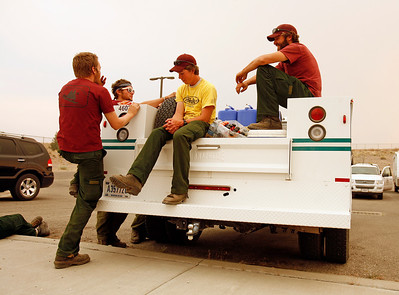 """(R-L) Dan Sebern and Kelly Chappell wait for instructions with their fellow """"hand crew"""" members after driving in from Utah, arriveing to help with firefighting efforts at a new base camp set up at Española Middle School on July 1, 2011.  Natalie Guillén/The New Mexican"""