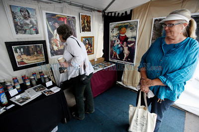 People look at paintings by Alex Chavez on Lincoln Ave at Contemporary Hispanic Market on July 24, 2010, in downtown Santa Fe.                   Luis Sanchez Saturno/ The New Mexican.