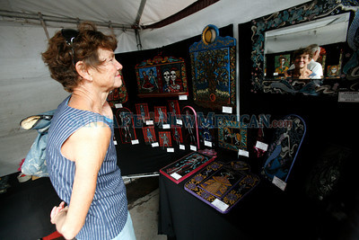 A woman looks at work by people walk by Pamela Enriquez-Courts on Lincoln Ave at Contemporary Hispanic Market on July 24, 2010, in downtown Santa Fe.                   Luis Sanchez Saturno/ The New Mexican.