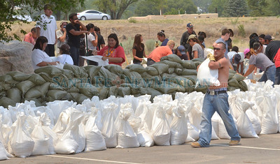 Lucas Naranjo carries a sand bag to the pile at the Santa Clara Recreation Center on Thursday, July 7, 2011. Naranjo was hard at work with several other volunteers filling sandbags.  Clyde Mueller/The New Mexican  Approximately 30 volunteers helped fill and stack hundreds of sandbags at the Santa Clara Recreation Center on Thursday, July 7, 2011. The Santa Anna Pueblo will use the sandbags to help protect against the runoff that may flood parts of the Pueblo.  Clyde Mueller/The New Mexican