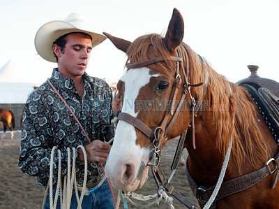 "Chase Massengill, of Pojoaque, N.M., gets his horse ready for the ""Tie-down Roping"" event during Rodeo de Santa Fe at the Santa Fe Rodeo Ground on June 23, 2011.  Natalie Guillén/The New Mexican"