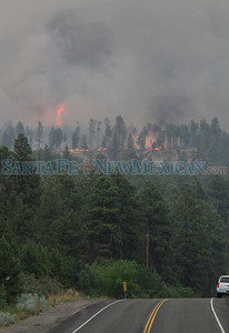 Flames are visible on a ridge facing Pajarito off of state road 501 during the second day of the Las Conchas Fire in  Los Alamos on Tuesday, June 28, 2011.  Photos by Jane Phillips/The New Mexican