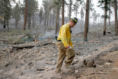 Brad Pitassi, PIO, Public Information Officer of the Southwest area Incident Management Team walks by a fire stump near the La Cueva Fire District on the second day of the Las Conchas Fire in  Los Alamos on Tuesday, June 28, 2011.  Photos by Jane Phillips/The New Mexican