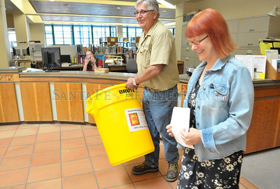 George Lopez of The Food Depot in Santa Fe, New Mexico and Amy Mullin, Librarian at the main Santa Fe Library (from left) on Washington take a 30 gallon food bin to a location by the front entrance of the library Tuesday June 28, 2011. Lopez distributed 22 food bins throughout Santa Fe where people can give donations of food to be given to victims of the Las Conchas fire.  Clyde Mueller/The New Mexican