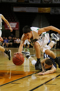 Mora's Derek Hurtado, number 22, steps over Santa Fe Prep's D.J. Casados, number 22, as he goes for a loose ball during the second quarter of the Mora vs Santa Fe Prep at the Santa Ana Star Center in Rio Rancho during the Basketball State Championship on Mar. 7, 2012.  Photo by Luis Sanchez Saturno/The New Mexican