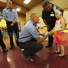 Gracie Hawkins, 5, a kindergarten student at Agua Fria Elementary School, gets congratulated by firefighter Mike Rivera, Station 3, on Wednesday, May 7, 2014, after being presented with the Roadrunner Hero Award during a school assembly. Hawkins saved her mother from a diabetic seizure the Sunday after Easter. Luis Sanchez Saturno/The New Mexican