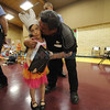 Gracie Hawkins, 5, a kindergarten student at Agua Fria Elementary School, gets congratulated by her grandfather, Ernie Lopez, and her mother, Darlene Lopez, on Wednesday, May 7, 2014, afer being presented with the Roadrunner Hero Award during a school assembly. Luis Sanchez Saturno/The New Mexican