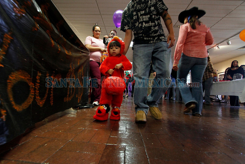 Joe Villegas, from Santa Fe, holds his daughter Arabella, 21 months, up as she collects candy with her Elmo costume at the Halloween Fall Festival at the Santa Fe Community College on Oct, 31, 2011.<br /> <br /> Photo by Luis Sánchez Saturno/The New Mexican