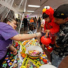Joe Villegas, from Santa Fe, holds his daughter Arabella, 21 months, up as she collects candy with her Elmo costume from Feliz Larrañaga, 15, at the Halloween Fall Festival at the Santa Fe Community College on Oct, 31, 2011.<br /> <br /> Photo by Luis Sánchez Saturno/The New Mexican