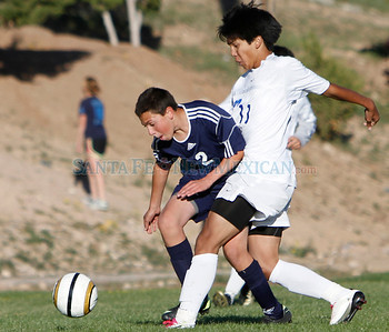Keenan Amer (left), of Santa Fe Prep, is fouled by Lorenzo Pasqual, of St. Michael's High School, during a boys soccer game in Santa Fe, N.M. on Oct. 10, 2011. After the foul was called, Pasqual kicked the ball away in frustration and received a yellow card.  Natalie Guillén/The New Mexican