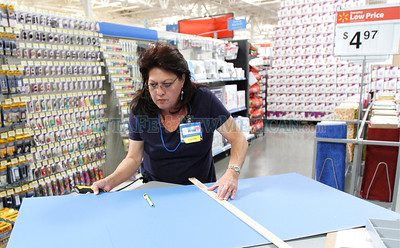 Walmart employees finish preparing for the grand opening on Tue., Oct. 11, 2011.  Natalie Guillén/The New Mexican