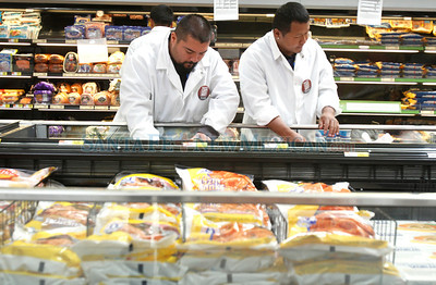 (L-R) Vincent Kavanaugh and Kunga Phuntsok work in the meat market as walmart employees finish preparing for the grand opening on Tue., Oct. 11, 2011.  Natalie Guillén/The New Mexican