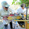 Juan Jose Gonzales, from La Cienega, and his son, John Paul Gonzales, grind up apples to press into cider at El Rancho de Las Golondrinas' Harvest Festival on October 6, 2012. Photo by Luis Sánchez Saturno/The New Mexican