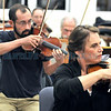 Santa Fe Community Orchestra members Clark Griffith and Janet Cordova (concert master) from left, play the violin during rehearsal.<br /> Clyde Mueller/The New Mexican