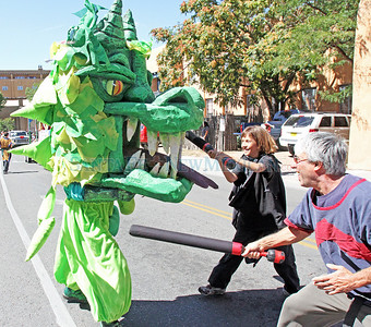Gigi Monroe (center) and Maury Brooks (right) use padded swords to play-fight a costumed dragon to promote the Renaissance Fair during the Historical/Hysterical parade on Sunday, Sept. 12, 2010 in Santa Fe, N.M..  Natalie Guillén/The New Mexican