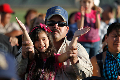 Jose Tavarez, from Santa Fe, uses his daughter Vanessa's hands, 7, to applaud the Payashow & Co clown performance at the Municipal Recreation Complex on Sep. 16, 2011, during the Mexican Independence Day celebration.  The food vendors and entertainment attracted over 2000 people to the celebration.  Photo by Luis Sánchez Saturno/The New Mexican