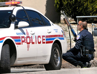 Armed Santa Fe City police officers block the northbound entrance to Camino Lado on Siringo Rd. Tuesday afternoon April 6, 2010. It was confirmed by the officers that a man with a gun was on the roof of a home near the intersection.  Clyde Mueller/The New Mexican