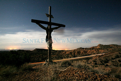 A cross overlooking Juan Medina Rd as Pilgrims make their way to the Santuario de Chimayo on April, 1, 2010, at 5:00 a.m.            Luis Sanchez Saturno/ The New Mexican.