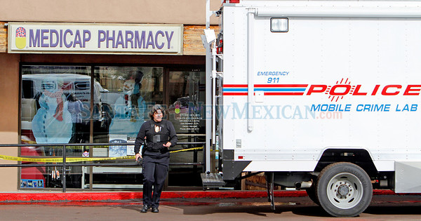 Patrol officer Laurie Kovach walks out of the Medicap Pharmacy at the Rodeo Plaza on Dec. 21, 2010. A man (not yet identified) was arrested about 20 minutes after robbing the pharmacy.          Photos by Luis Sanchez Saturno/The New Mexican