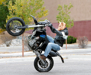 Daniel Coriz practices some wheelies, wearing a halloween mask. in the DeVargas shopping center on his lunch hour, from DOT,  on Monday, October 25, 2010.  Coriz is also a member of the stunt series competitions.  Photos by Jane Phillips/The New Mexican