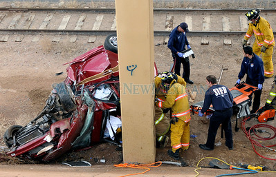 Santa Fe Firefighters and EMT's attend to the driver involved in a rollover accident at the overpass of St. Frances Rd. and I-25 early Monday morning January 18, 2010.  Clyde Mueller/The New Mexican