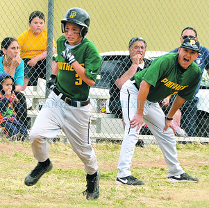 Head coach Augustin Ruiz (right) shouts at his player Eli Varela to run hard from third base and score during the first inning of the District 6AA, Monte del Sol at Pecos baseball game played at Pecos High School Wednesday, April 18, 2012.Clyde Mueller/The New Mexican