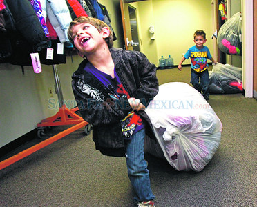 Gabe Lujan,6, his younger brother, Rico,4, carry coats out for the 22nd annual Christus St. Vincent Regional Medical Center Cozy Coats for Kids drive on Friday, November 16, 2012.   The hospital collects new coats for needy elementary school children in Santa Fe.  Over 759 coats were distributed to over twenty elementary school.  Jane Phillips/The New Mexican