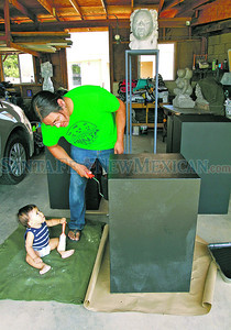 Jesse Peshlakai,1, watches his father, Kenneth Peshiakai, puts some finishing touches on his pedal steels for his first Indian Market on Tuesday, August 14, 2012. Peshiakai who is an IAIA graduate will be selling sculptures and jewelry in front of the Five and Dime store.  Jane Phillips/The New Mexican