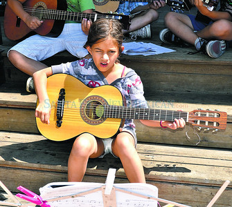 """Emma Reynolds, 8 year old student at El Dorado Community School strums her guitar and sings, """"He's Got The Whole World in His Hands"""" along with other students enrolled in the Santa Fe Public Schools' summer music camp program led by teacher Brandelyn Davidson play their guitars and sing for passersby's at 11 a.m. at the Santa Fe Plaza Band Stand on Friday, June 22, 2012. Clyde Mueller/The New Mexican"""