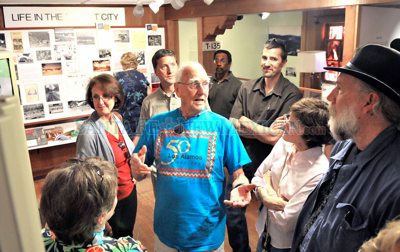 During a tour of the Los Alamos Historical Museum Robert Carter (center with blue T-shirt) tells his sons and daughters stories about some of the people he worked with when he was a Manhattan project scientist at Los Alamos National Laboratory on Friday, July 16, 2010 morning. Carter, who raised 11 children on the hill, is celebrating his 90th birthday in Santa Fe Saturday night. Colleagues from the 1940s and 1950s will be joining the celebration along with family and friends. In all there are 55 adults from the family with spouses as well as 10 grandchildren.<br /> Clyde Mueller/The New Mexican