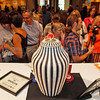 Collectors, fans and reporters gather around Jeremy Frey after the 2011 Best of Show ceremony at the Santa Fe Indian Market on Aug. 19, 2011. His winning piece is made of sweet grass and black ash and is in the contemporary style. He calls it a pointed vase.<br /> <br /> Photo by Luis Sánchez Saturno/The New Mexican