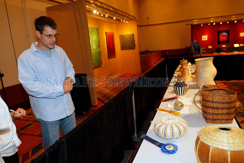 Jeremy Frey checks to see what award one of his baskets one before the Best of Show ceremony at Indian Market at the Santa Fe Community Convention Center on Aug. 18, 2011.<br /> <br /> Photo by Luis Sánchez Saturno/The New Mexican